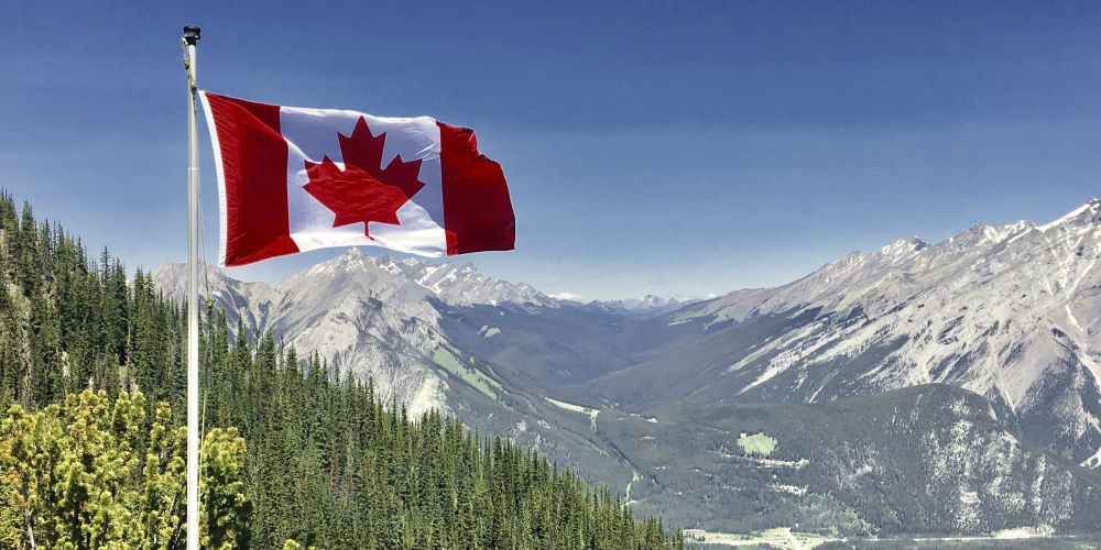 Canada flag in front of mountain landscape