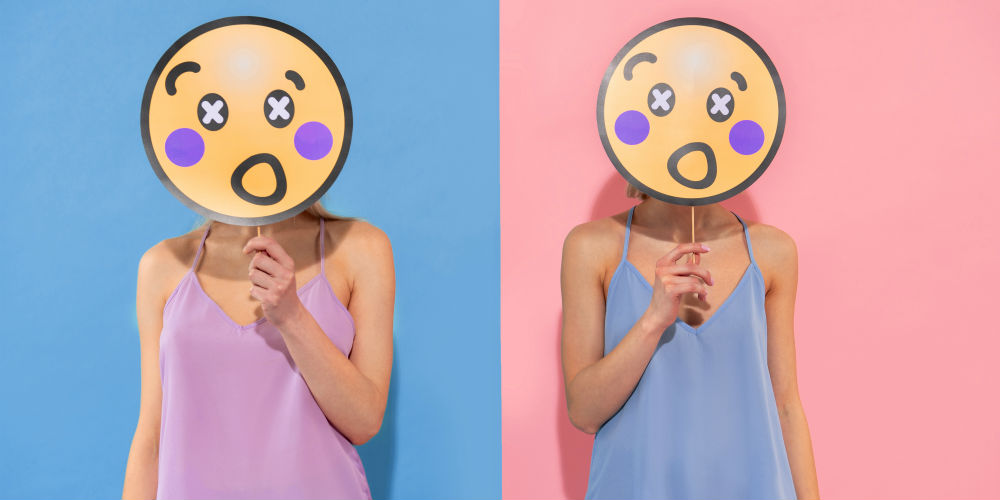 Two people standing next to each other holding emojis in front of their faces